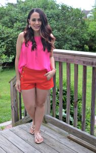 Melissa Mom with Style wearing a pink top from Francesca, pairing it with J.Crew red shorts