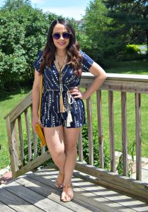 Melissa Mom with Style wearing a Bella V Mobile Boutique arrow and tassel romper with flat sandals and a mustard clutch