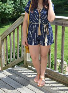 Melissa Mom with Style wearing a navy blue arrow print romper with brown accessories