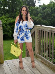 Melissa Mom with Style wearing a white and blue floral Bella V Boutique romper with neon accessories
